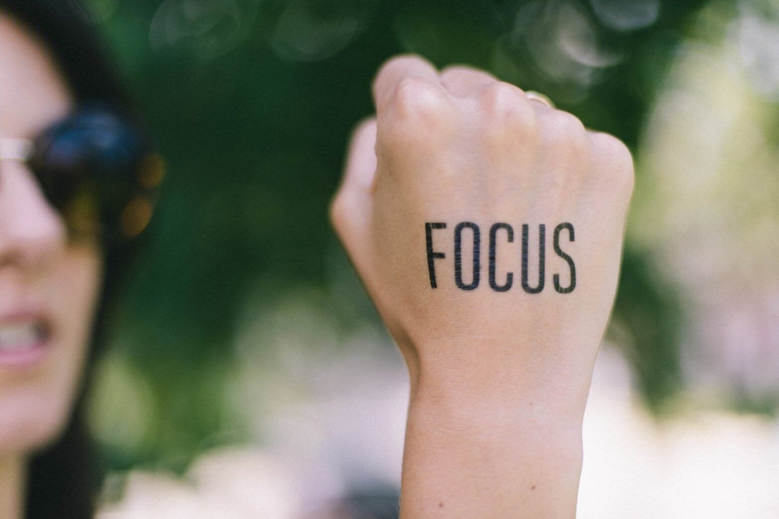 girl wearing a motivational tattoo on her hand