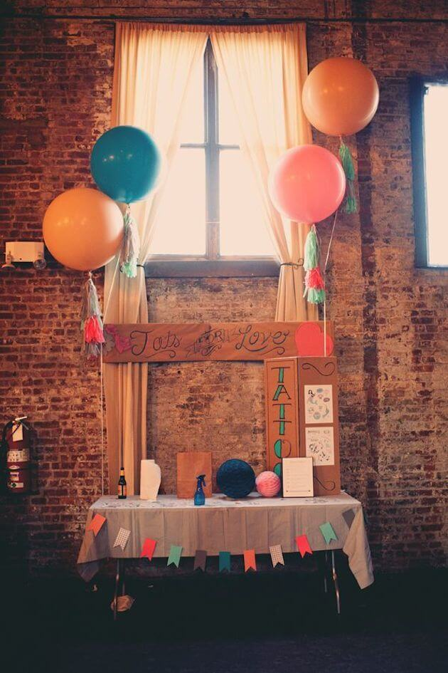 homestyle diy fake tattoo station with balloons and colorful bunting