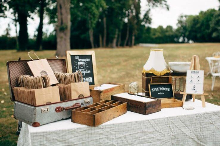 outdoor vintage wedding temporary tattoo station with tiny boxes