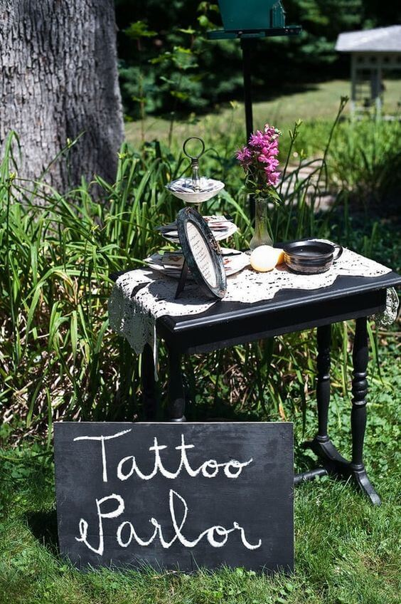 fresh outdoor wedding temporary parlour with tattoos placed on a black table