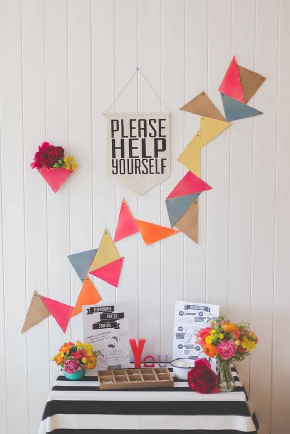 colorful origami wedding temporary tattoo station with flowers, tattoo, and signage 'please help yourself'