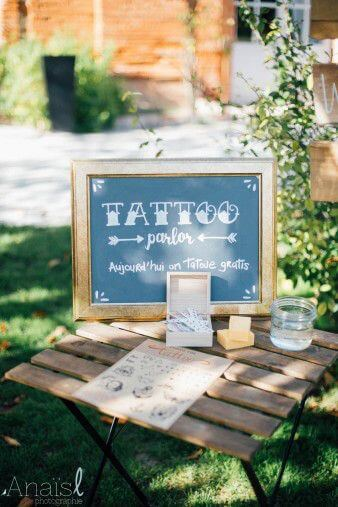 brass-rimmed blackboard announcing temporary tattoo parlour on a simple table