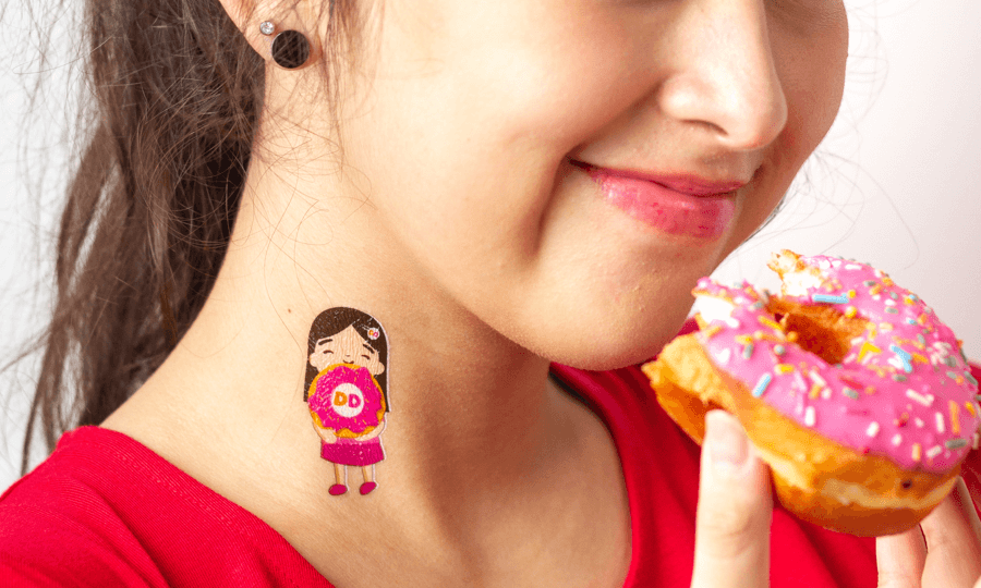 A girl in red t-shirt with a Dunkin Donut multi colored custom temporary tattoo attempts to eat a donut
