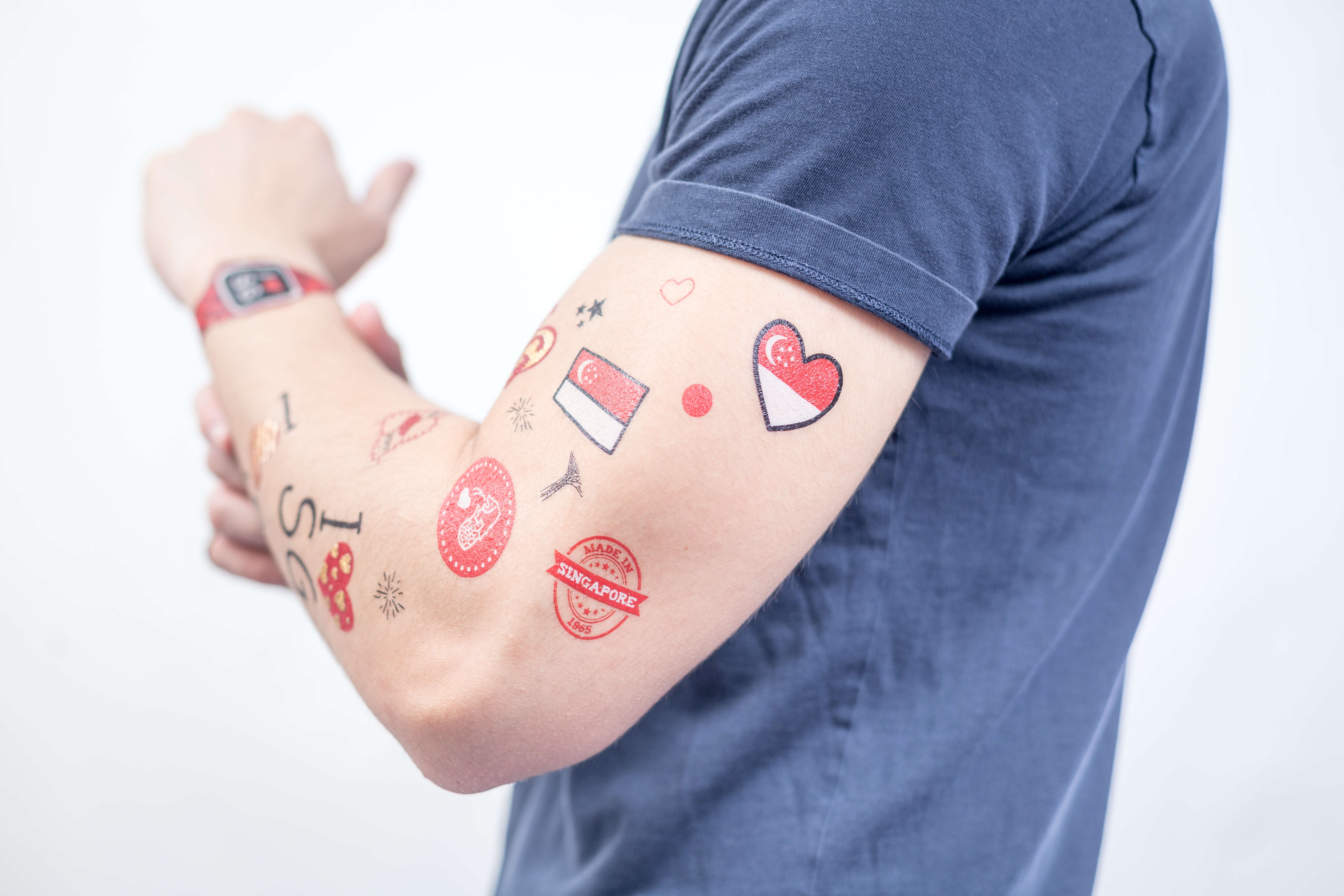 red and white NDP fake tattoos in various designs on arm of a man clad in dark grey t-shirt