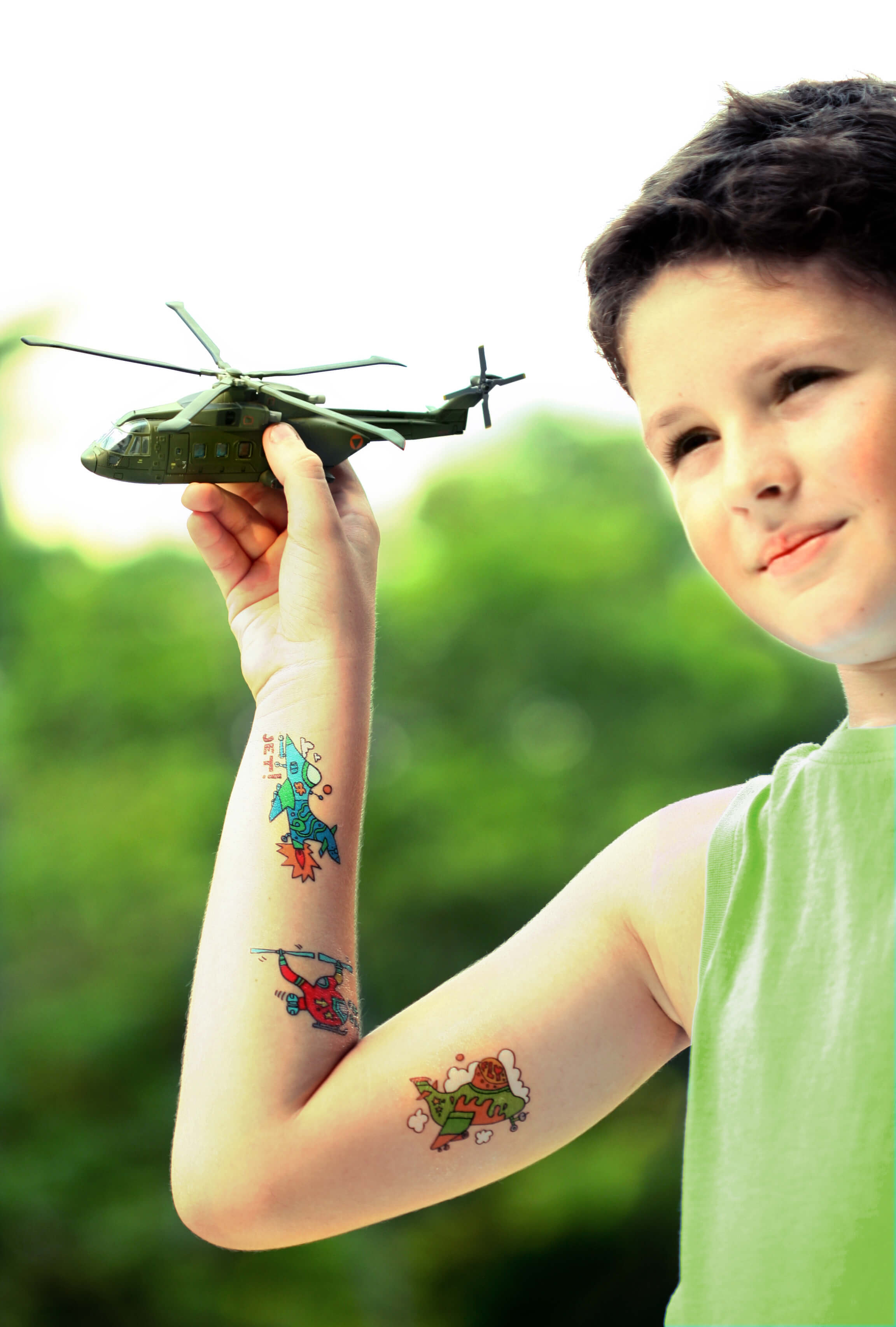 a kid holding chopper in his hands and wearing jet and chopper tattoos on his hands