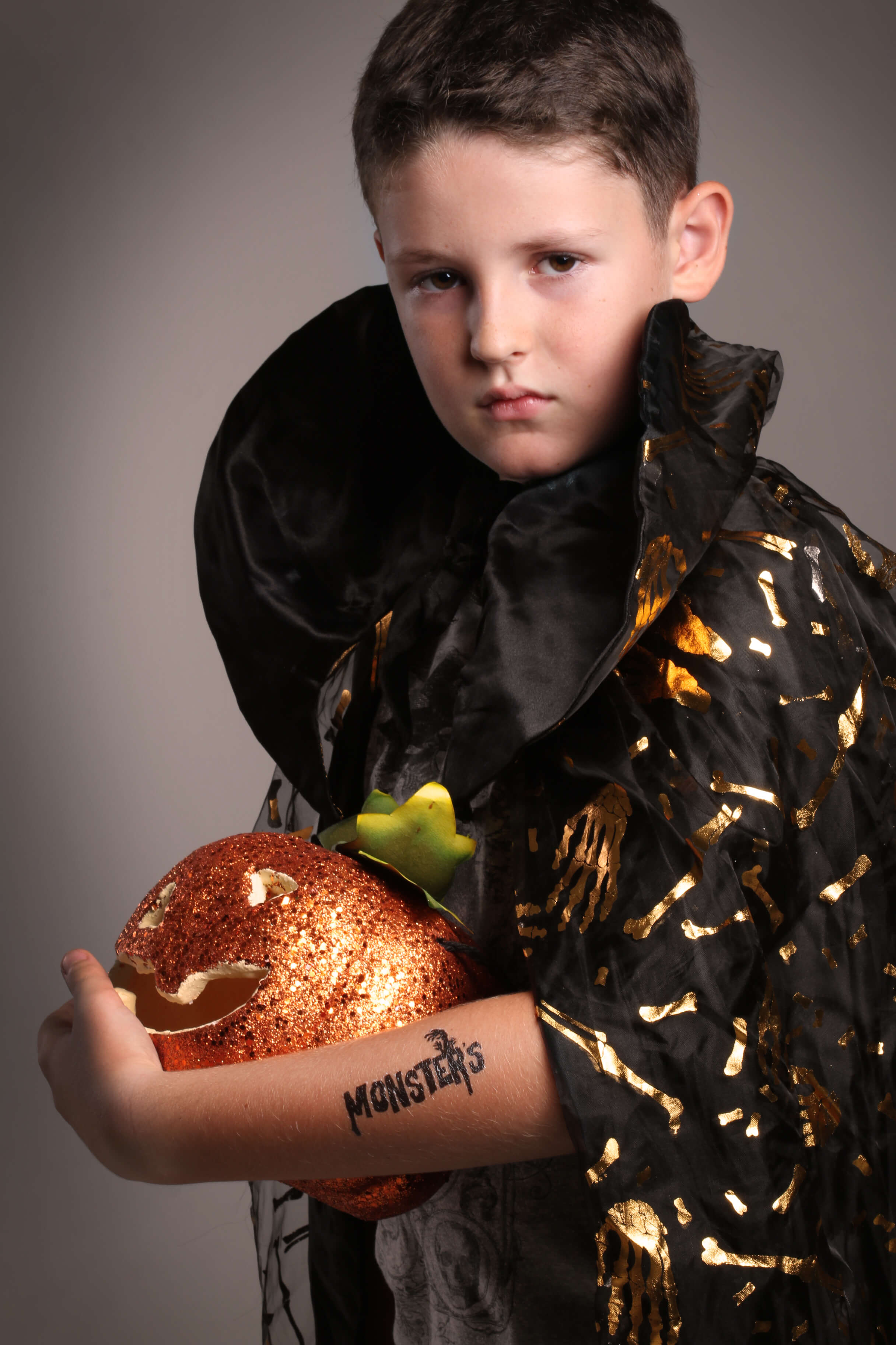 boy in halloween gape holding a scary carved pumpkin and wearing spooky tattoo