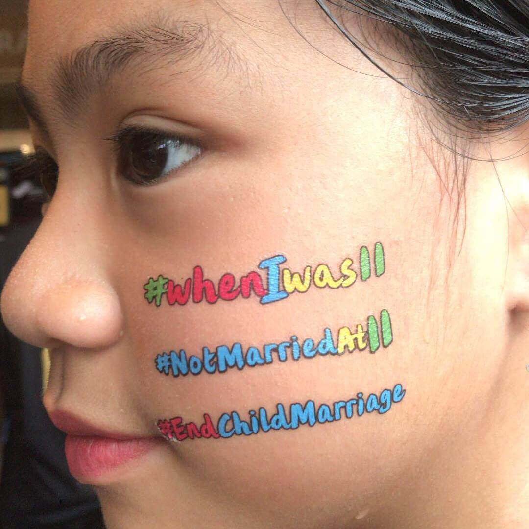 Cause temporary tattoo protesting against child marriage on cheek of a girl at The Body Shop's event in Malaysia