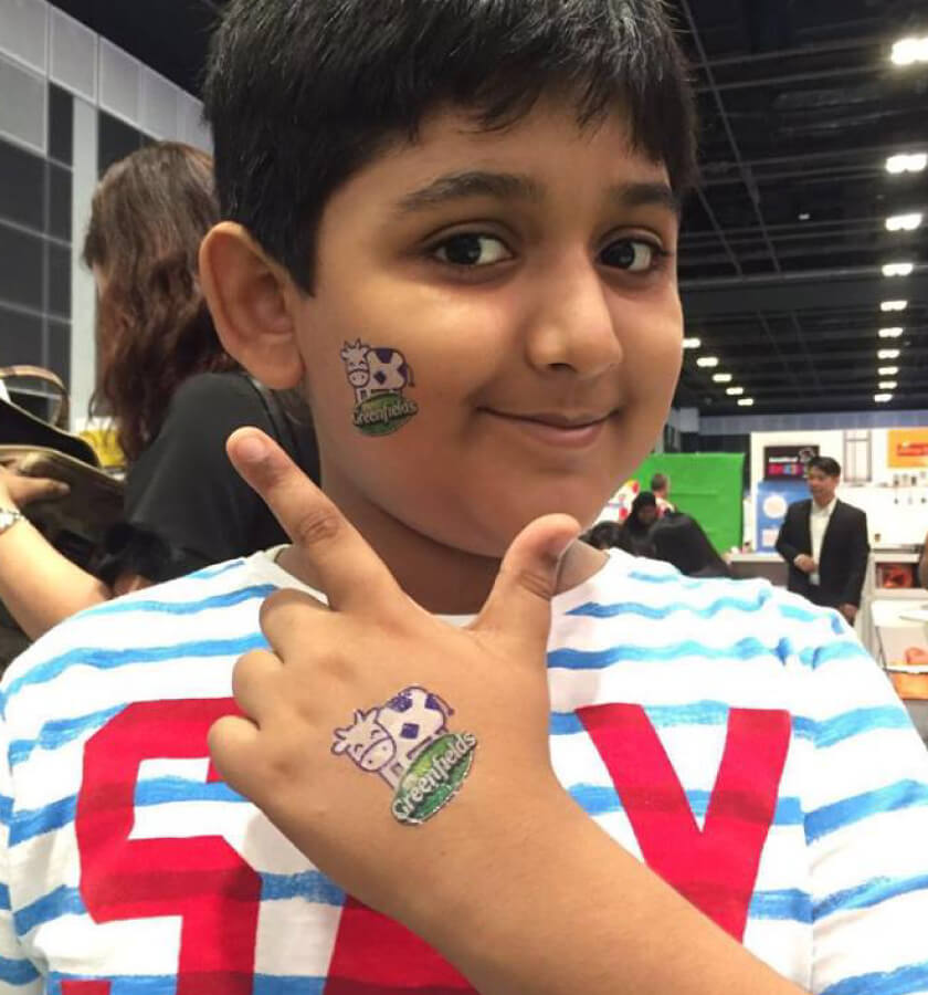 A smiling kid shows his Greenfields Milk promotional temporary tattoo at Kids World Fair, Singapore