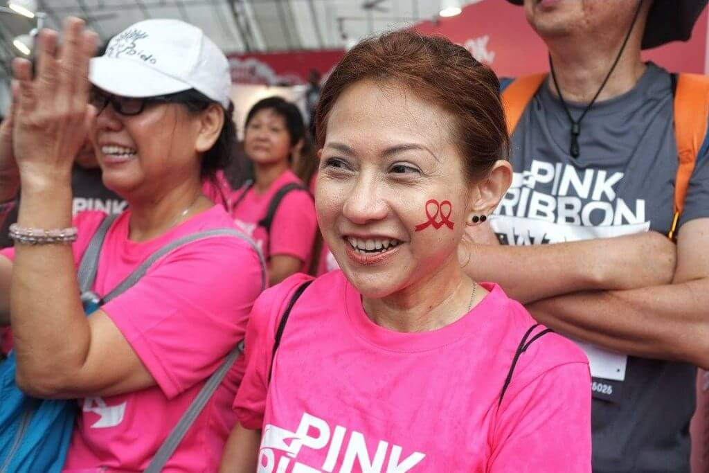 smiling woman participant of pink ribbon walk with her custom pink ribbon tattoo on her cheek