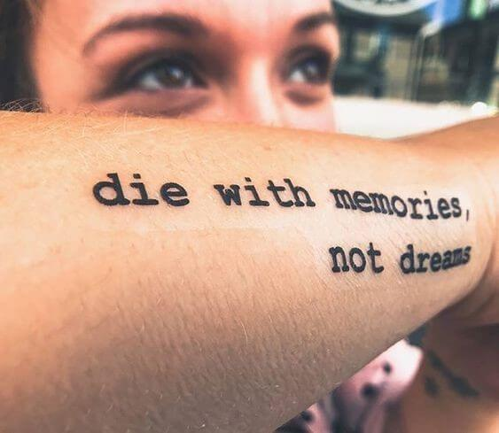 man showing off die with memories not dreams fake tattoo on arm