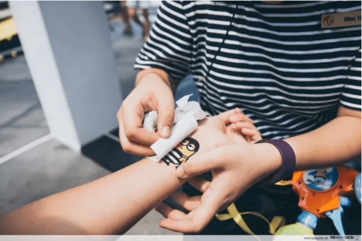 a volunteer putting a minion temporary tattoo on a customers wrist at universal studions