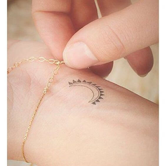 fake crescent moon tattoo on woman's wrist