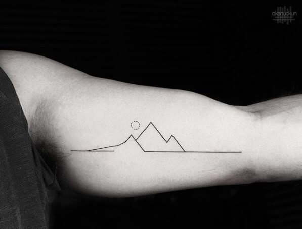 simple linear mountain tattoo with rising sun on arm