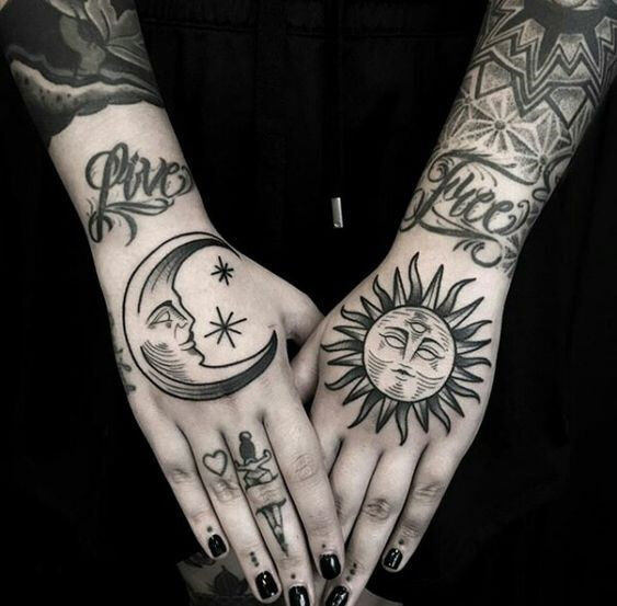 heavily tattooed arms with sleepy moon tattoo on one hand and sleepy sun tattoo on another