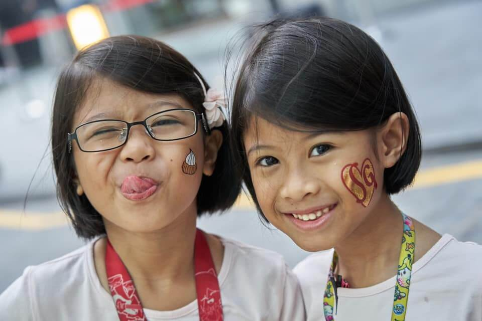 two kids with temporary tattoos on cheeks at gai gai carnival