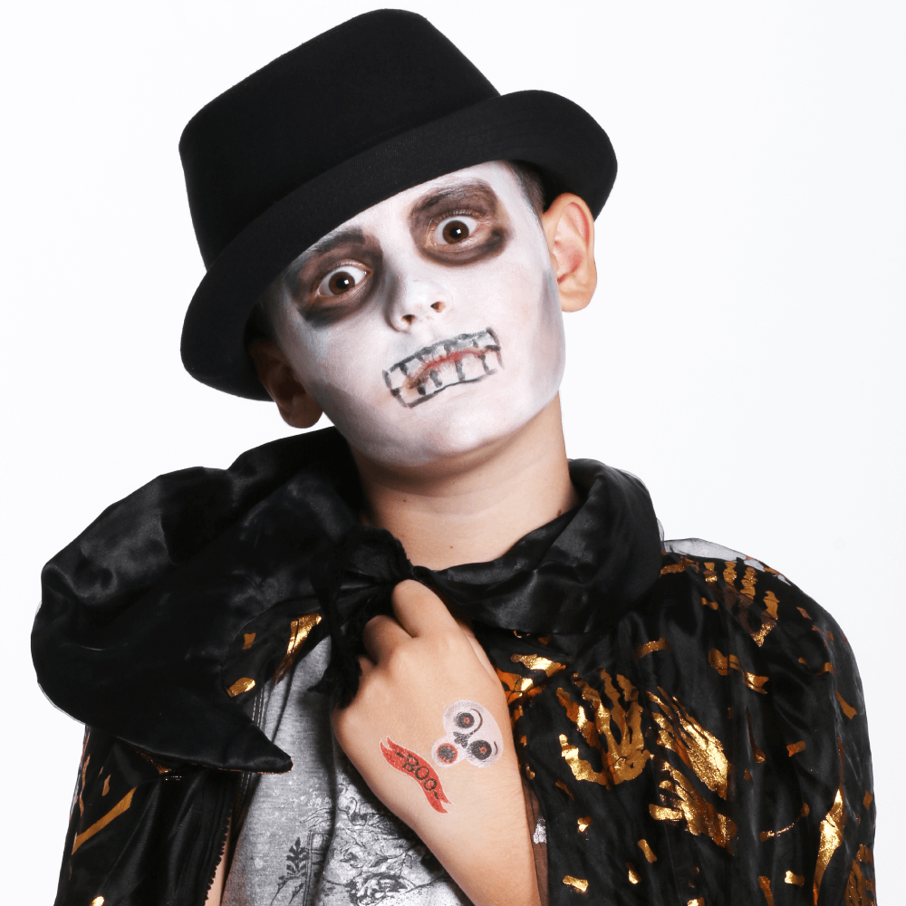 boy dressed as a zombie poses with his halloween skull temporary tattoo