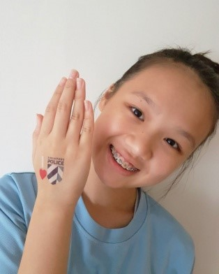 "Smiling child in blue t-shirt and braces holds up her 'I love Singapore Police"" temporary tattoo"